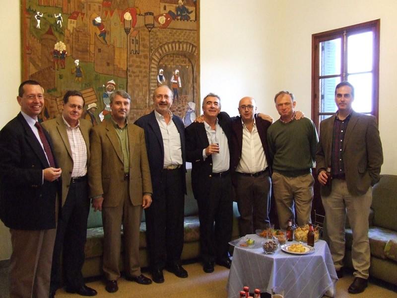 varios señores de pie en un salón, cogidos por los hombres mientras sonríen a la cámara. Están tomando copas de champán y aperitivo
